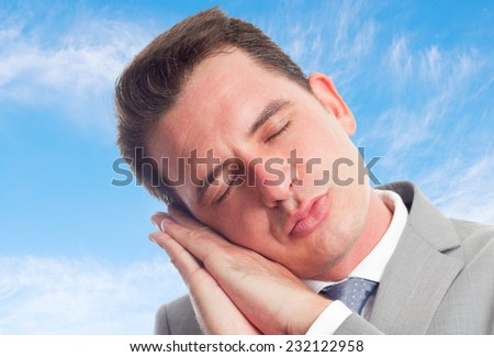 Young business man with grey suit over clouds background. Looking sleepy - stock photo
