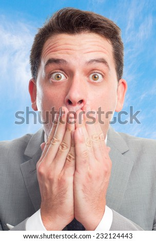Young business man with grey suit over clouds background. Looking surprised