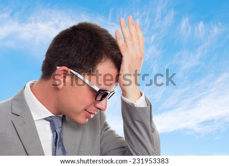 Young business man with grey suit over clouds background. Looking tired