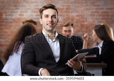 Young business man with his staff at the meeting in a conference room