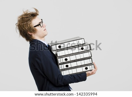 Young business man with nerd glasses and carrying a bunch of folders - stock photo