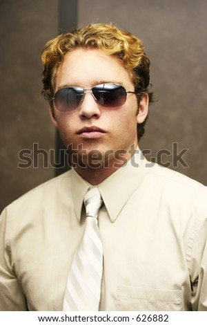 young business man with sunglasses on in the office - stock photo