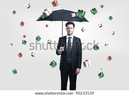 Young Business man with umbrella under gift boxes rain. On a gray background.