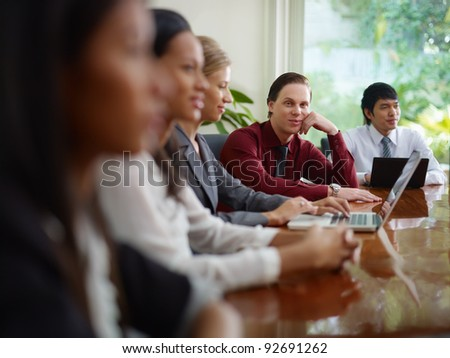young business man working as manager and smiling at camera during meeting with colleagues - stock photo