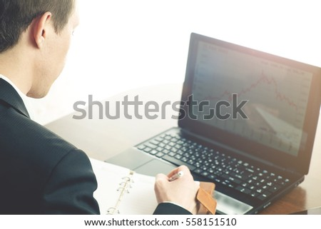 Young business man working at office with laptop on his desk