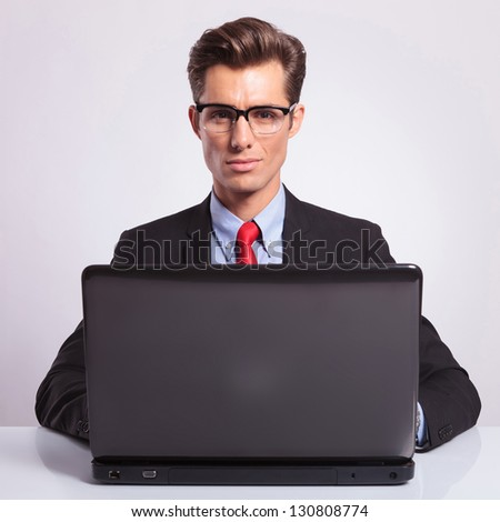 young business man working on a laptop at the desk and looking at the camera, on gray background - stock photo