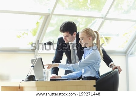 Young business man working together with her colleague on laptop in office. Shallow focus.