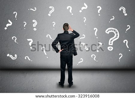 Young business man write question mark on blackboard
