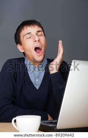 Young business man yawning in front of laptop and cup of tea or coffee - stock photo