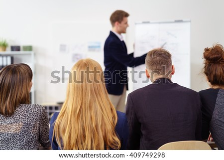 Young business manager giving a presentation, view over the backs of four diverse colleagues sitting listening to him - stock photo