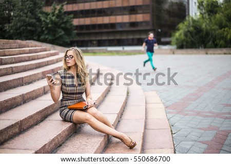 Young business or student woman using cell mobile phone and hold in hand tablet computer or case with documents. Businesswoman sit on stoned stairs against office building on street. man run on date.