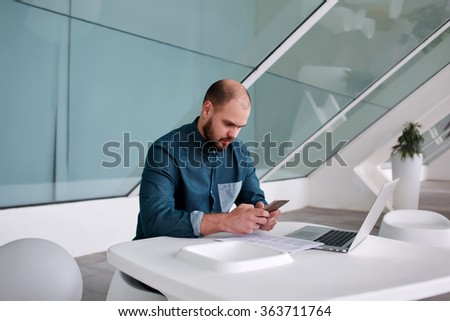 Young business owner reading text message on mobile phone after development report on net-book while sitting in office interior, handsome man chatting on cell telephone after work on laptop computer - stock photo