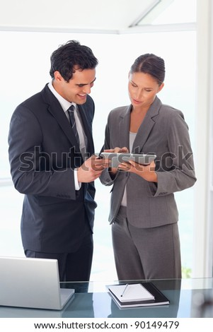 Young business partner looking at tablet together - stock photo