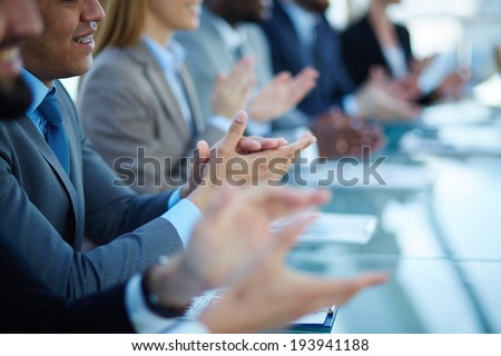 Young business partners applauding to reporter after listening to presentation at seminar - stock photo