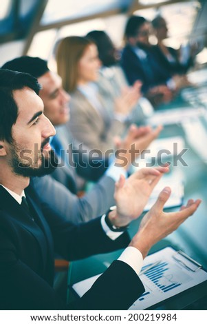 Young business partners applauding to reporter after listening to presentation at seminar