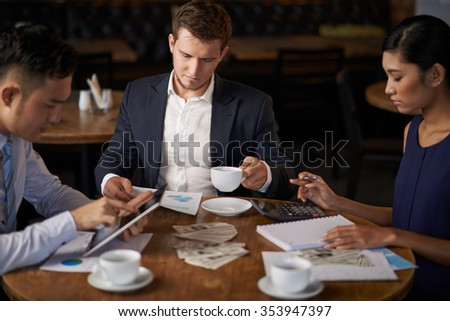 Young business partners counting revenue at the cafe table