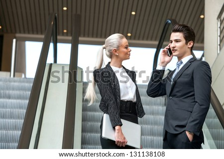 Young Business partners having conversation on escalator in mall. - stock photo