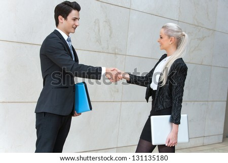 Young business partners shaking hands over deal outdoors. - stock photo