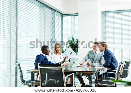 Young business people at meeting in office - stock photo