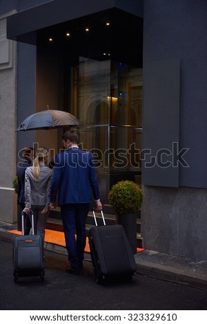 Young business people couple entering city  hotel, looking for room, holding suitcases while walking on street - stock photo