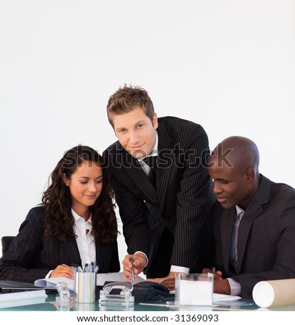 Young business people discussing in an office and looking at the camera