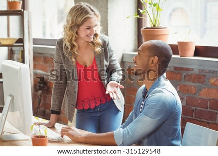 Young business people discussing in creative bright office - stock photo