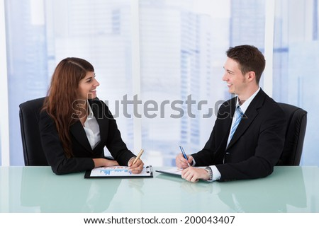 Young business people discussing over graphs at office desk