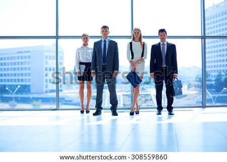 Young business people go down of modern office - stock photo