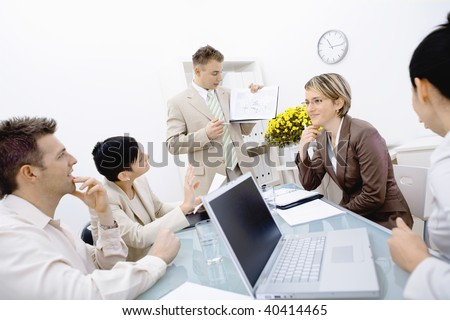 Young business people having a business meeting, sitting around table at office, businessman showing diagram. - stock photo
