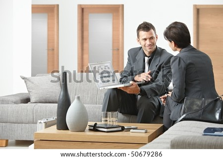 Young business people having meeting at office sitting on sofa working in team. - stock photo