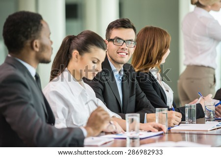 Young business people in suits sitting at meeting room and listening speaker.