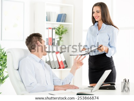 Young business people in the office, a woman standing next to office desk with a smile on her face gives the folder to young businessman who sits in office chair. - stock photo