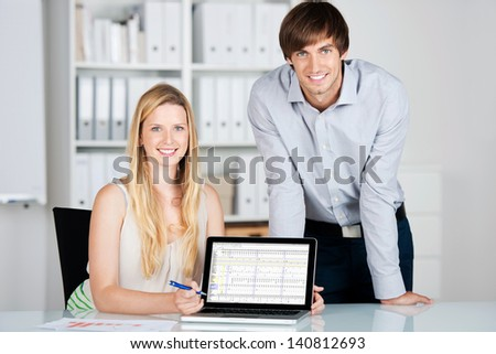 young business people presenting chart on laptop