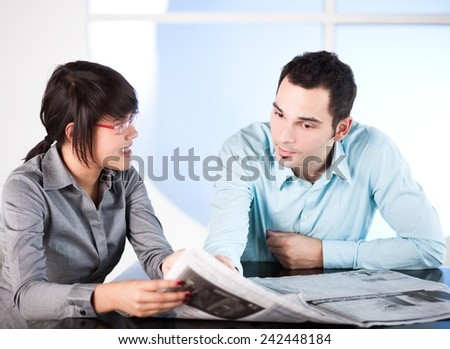 Young business people reading newspaper