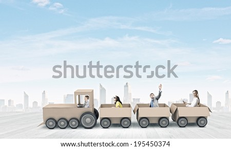 Young business people riding carton train. Teamwork concept - stock photo