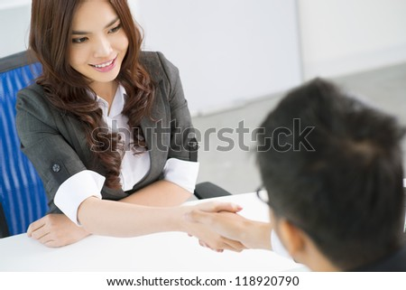 Young business people shaking hands in sign of their partnership - stock photo