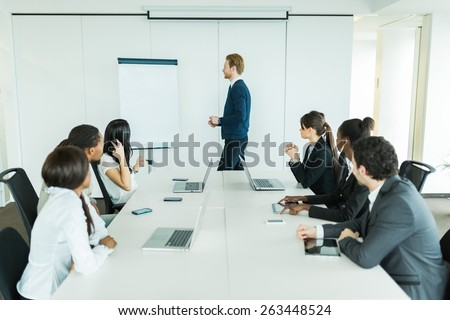 Young business people sitting at a conference table while listening to the lecturer - stock photo
