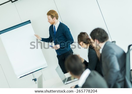 Young business people sitting at a conference table while listening to the lecturer  and learning new technologies from the leacturer who is pointing at the whiteboard - stock photo