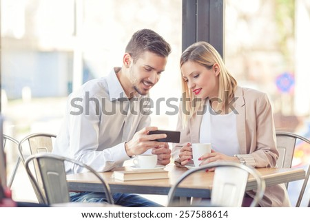 Young business people sitting in a coffee shop and looking at mobile phone. - stock photo