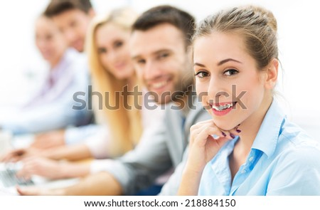 Young business people sitting in a row - stock photo