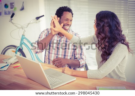 Young business people smiling at each other in the office - stock photo