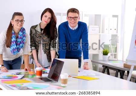 Young business people standing at office near desk. - stock photo