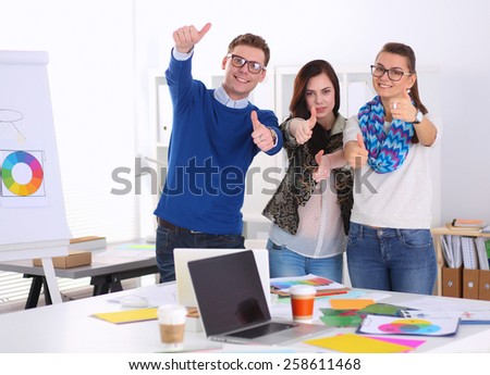 Young business people standing at office near desk and showing ok.