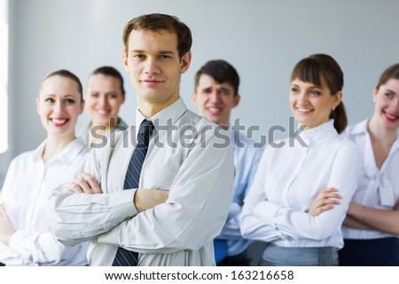 Young business people standing with arms crossed on chest