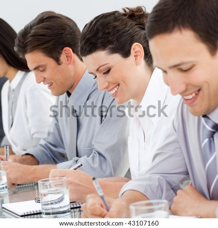 Young business people taking notes at a conference in the office
