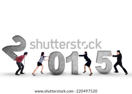 Young business people try to compose number 2015 in studio, isolated over white background - stock photo