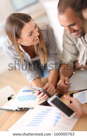 Young business people using smartphone in meeting