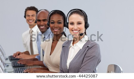 Young business people with headset on smiling at the camera in a call center
