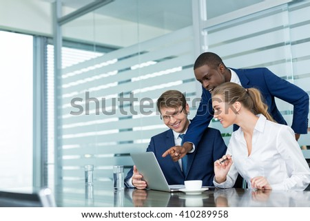 Young business people with laptop in office - stock photo