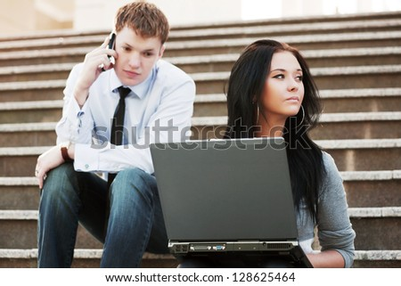 Young business people with laptop sitting on the steps - stock photo